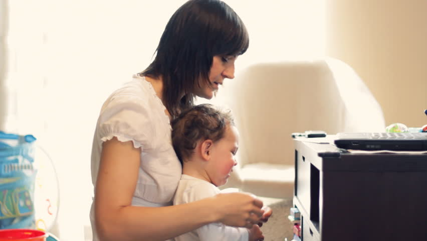 Young mother trying to work on laptop with kid interrupting, dolly shot - HD stock video clip