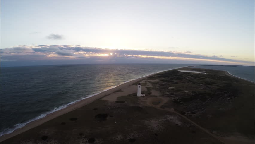 Lighthouse and beach aerial. Nantucket, Massachusetts. Aerial sunset with lighthouse. Beauty shot in 1080p HD. - HD stock video clip