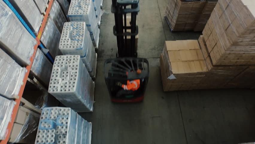 Aerial Overhead Shot of Working Forklift Loader inside Logistic Warehouse. Shot on RED Cinema Camera in 4K (UHD).