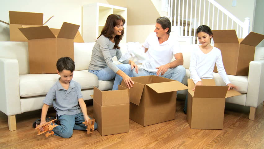 little boy with toy planes helping his family pack up empty cardboard boxes from moving home. Black Bedroom Furniture Sets. Home Design Ideas