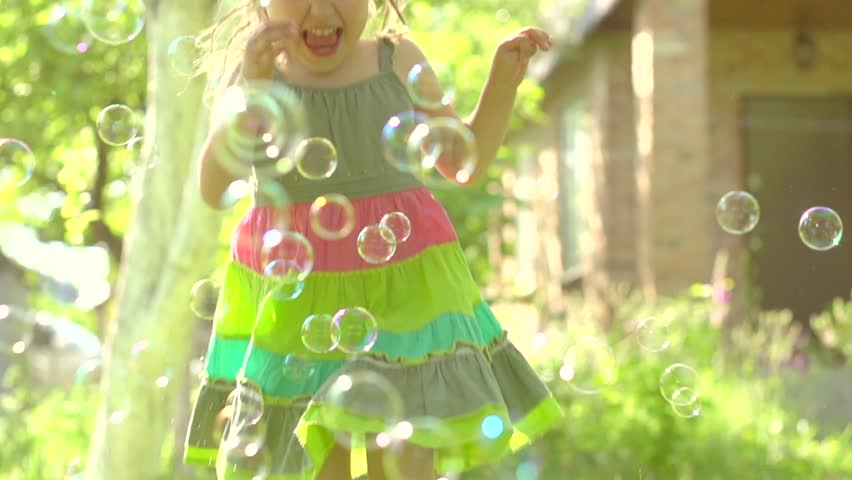 Happy Little Girl Playing Wit Soap Bubbles Outdoor