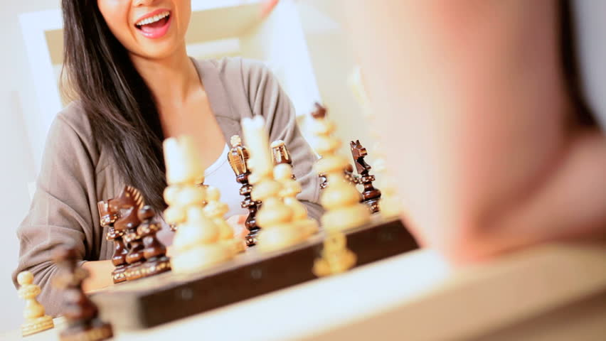 Pretty chinese girl making a winning move in a chess game - HD stock footage clip