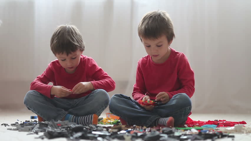 Little children playing with lots of colorful plastic blocks indoor, building a fire truck and a fire house, reading from a manual and imagining - HD stock footage clip
