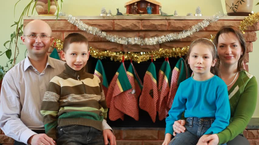 brother and sister sit parents in front of fireplace, smiling - HD stock video clip