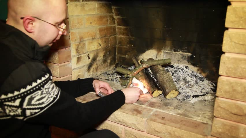 man in cardigan and spectacles kindle fire in fireplace - HD stock video clip