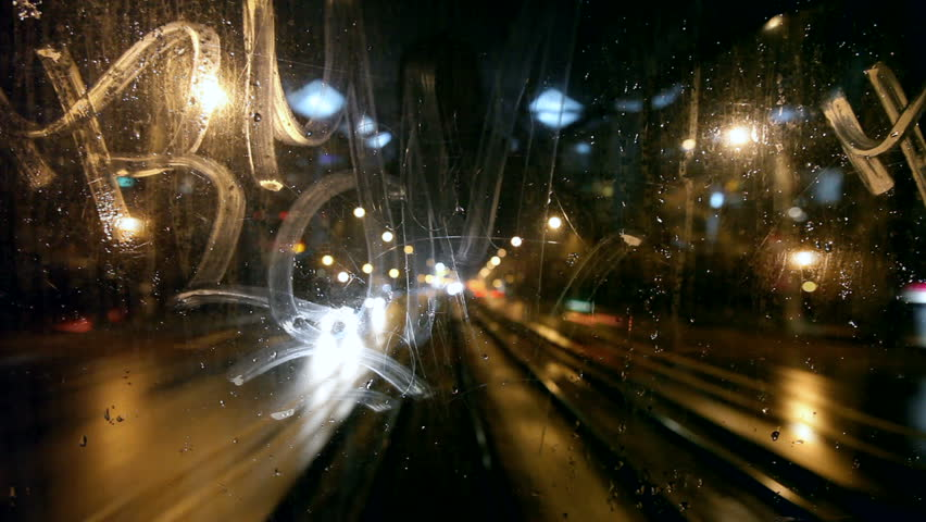 Tram's rear window view. Tram passes through tunnel. Cold rainy weather cityscape. Steamy window. Night time. Focus on window.