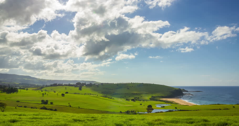 Spectacular time lapse of clounds moving gently across rolling green hills next to the ocean