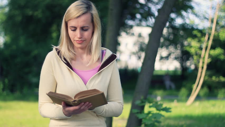 Attractive female student reading book in the park  - HD stock video clip