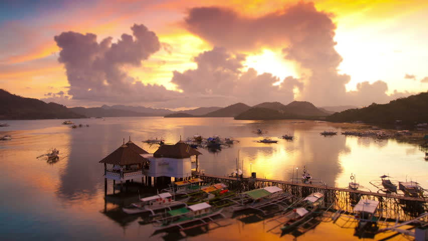 Sunset over Coron harbour timelapse, Coron, Palawan, Philippines. View on pier with traditional bangka boats