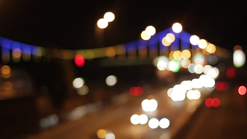 Blurred background of highway. Traffic of a night city. Rush hour on the road. Car lights of a night city. Footage of a night city. Evening traffic.