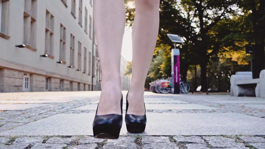 Sexy woman legs in black high heels shoes walking in the city urban street, crossing the road. Steadicam stabilized shot in Slow motion. Lens flare. Business woman Cinematic shot.