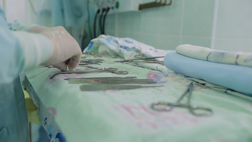 Nurse preparing medical surgical instruments before surgery