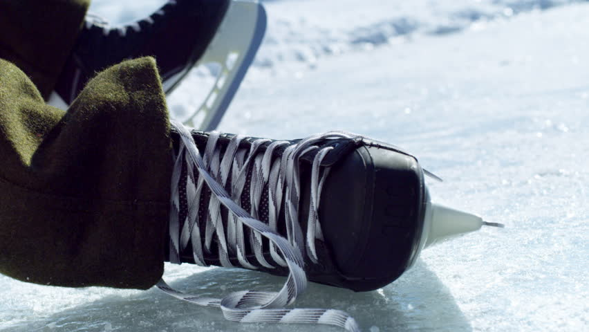 A close up shot of a hockey skate on an outdoor ice rink with a quick motion of beginning to tie the laces. - 4K stock video clip