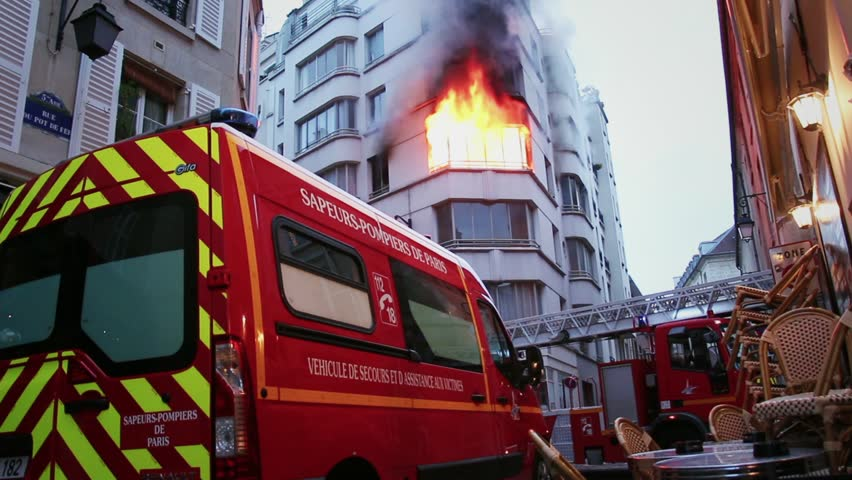 Fire truck in front of a building on fire. 4 OCTOBER 2015 - PARIS, FRANCE; An apartment explodes and catches fire, breaking all the windows and killing one person.
