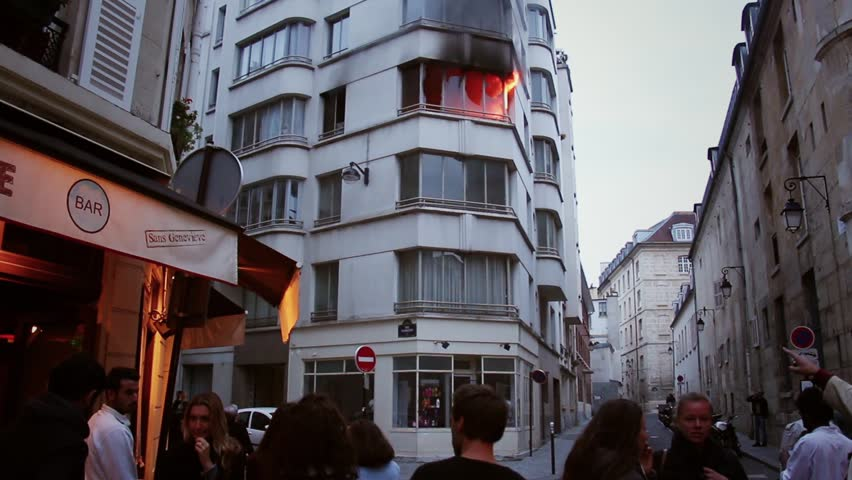 People watching from street a fire in apartment. 4 OCTOBER 2015 - PARIS, FRANCE; An apartment explodes and catches fire, breaking all the windows and killing one person.