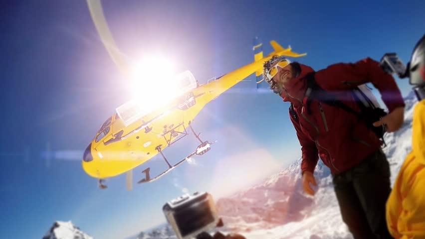 Actionsportlers were dropped by a helicopter at the top of the mountains. The sun is shining brightly in the blue sky. There is a mountain range in the background covered in snow.