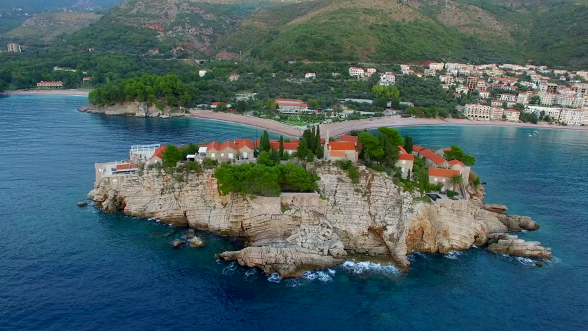 A helicopter flight over the island of Sveti Stefan in Montenegro. Aerial photography, video from a height, the height of bird flight. Flying over the sea, the coast and the Balkans - 4K stock video clip