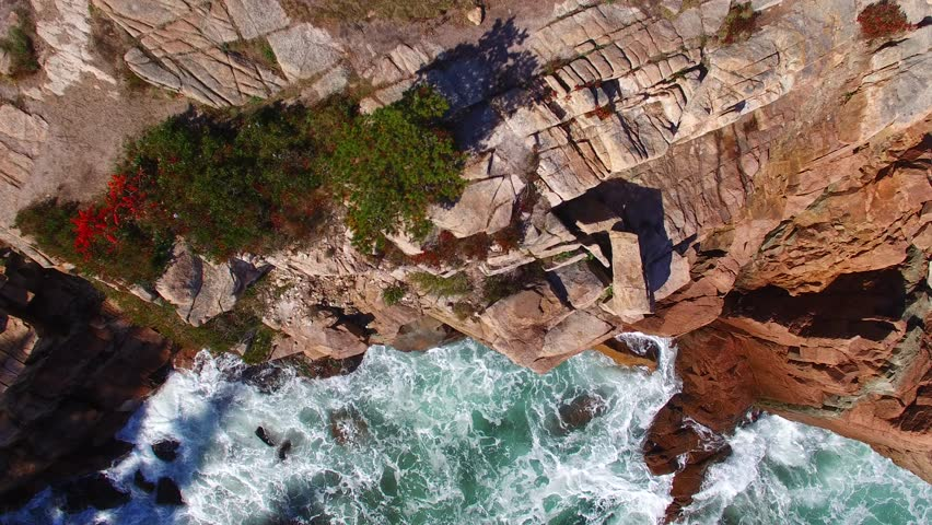 Spectacular cliffs over the ocean. Bird view of rocks, sea and foliage
