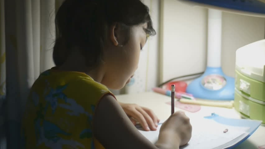 Young Asian girl doing her homework - HD stock footage clip