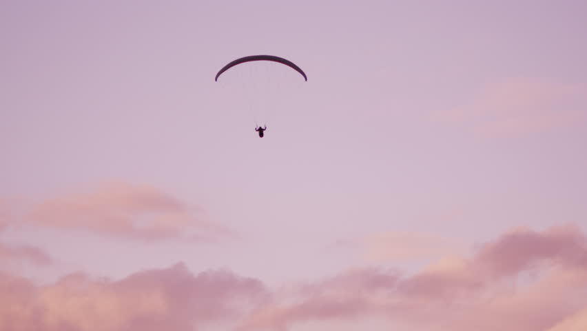 Telephoto shot of a paraglider soaring across valley amoung the pink clouds - 4K stock footage clip