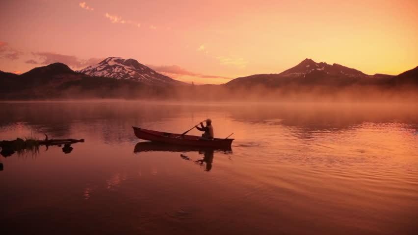 Cinemagraph - Man paddles canoe in lake at sunrise. Motion Photo.