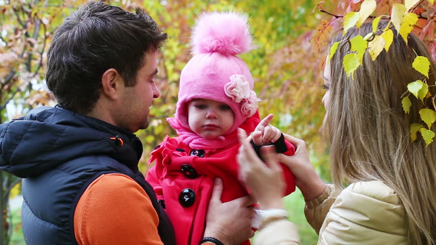 Happy Family With Small Child Walking In The Autumn Forest