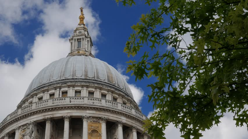 Static shot of the dome of St Pauls Cathedral in London framed by trees. White clouds and blue sky. Original footage is 4K - 4K stock footage clip