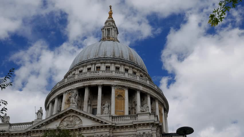 Static time-lapse of the dome of St Pauls Cathedral in London framed by trees. White clouds speed by. Original footage is 4K - 4K stock footage clip