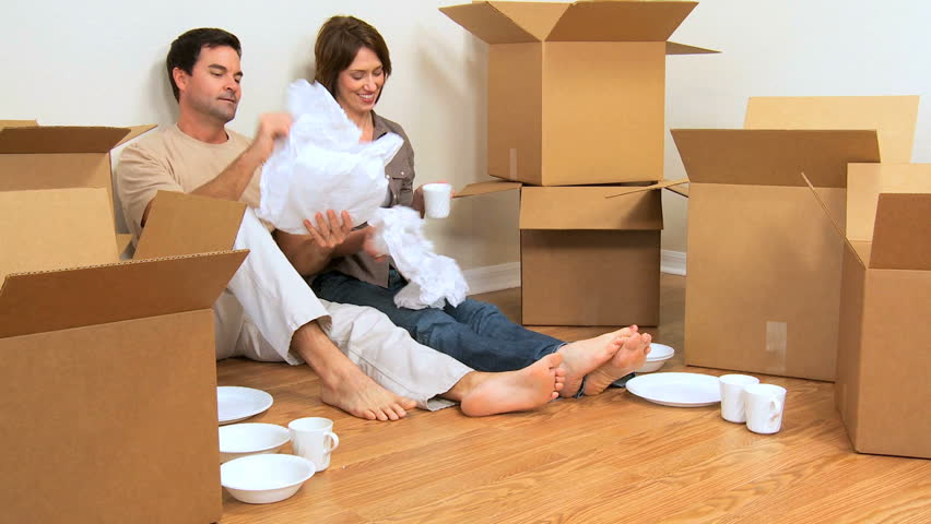 Happy caucasian couple exhausted from unpacking home moving boxes - HD stock video clip