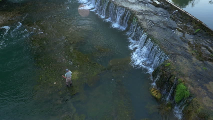 Aerial - Mature adult fly fishing near small waterfall