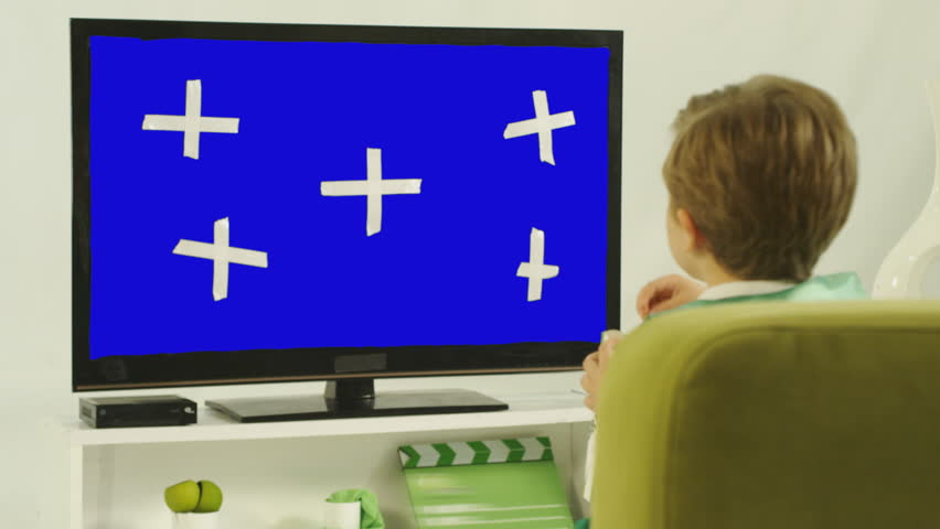 Child watching TV. Boy watching movie while eating popcorn in the white room. TV with blue screen and tracking marks .