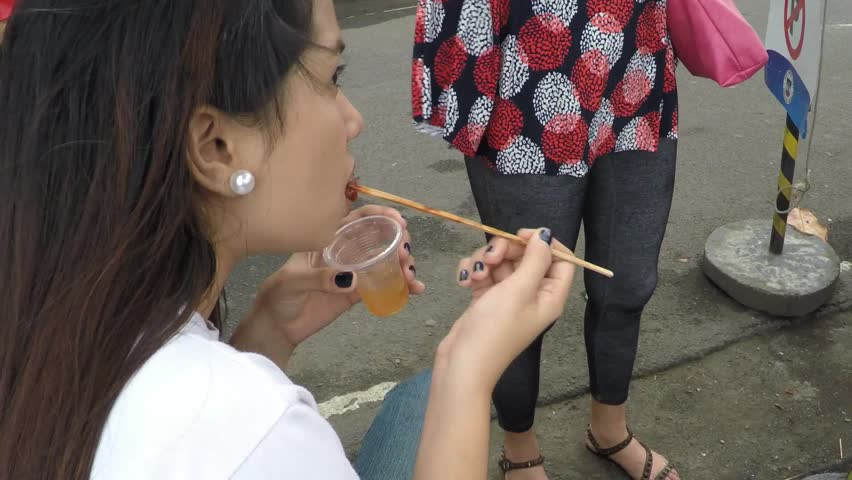 SAN PABLO CITY, LAGUNA, PHILIPPINES - NOVEMBER 14, 2015: Pretty lady eating broiled chicken feet