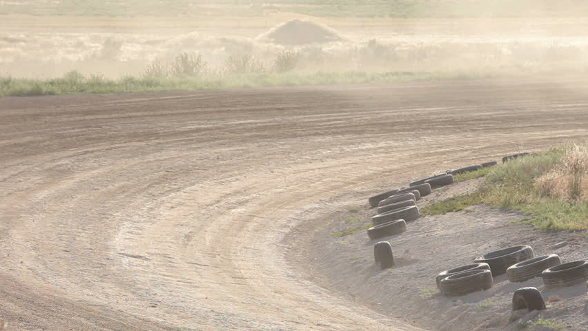 Race trucks on dirt oval course. Highly modified stock cars driving and racing on a very dirty and dusty track corner. Warmup lap testing the road and track conditions. - HD stock footage clip
