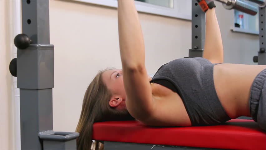 Bodyfitness workout. Bench press. Young woman doing exercises with fingerboard for rod in the gym