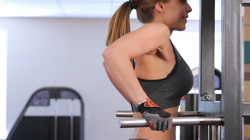 Bodyfitness workout. Pulling up on the bars. Young woman doing exercises in the gym