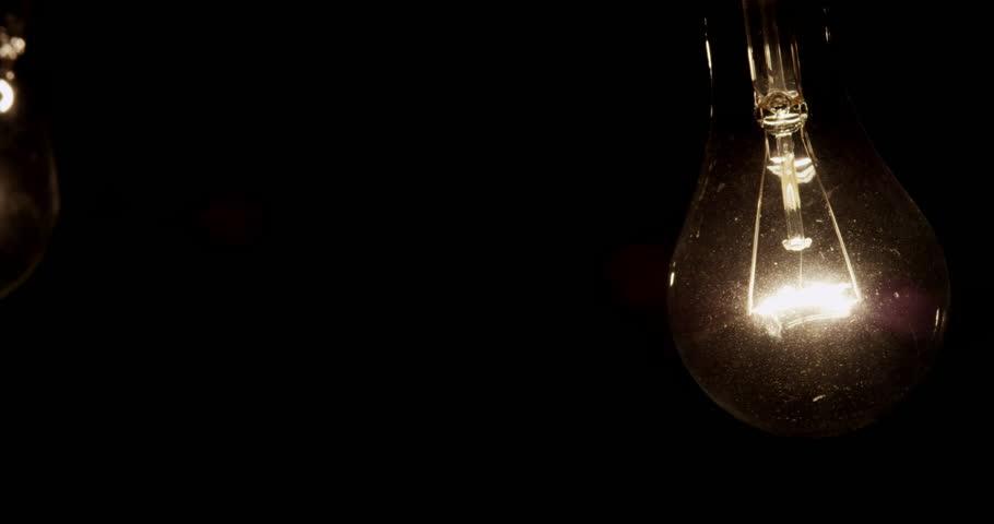 4K swinging filament light bulbs CU. Interrogation lighting. Shot with RED EPIC in 4K DCI Native Resolution UHD.