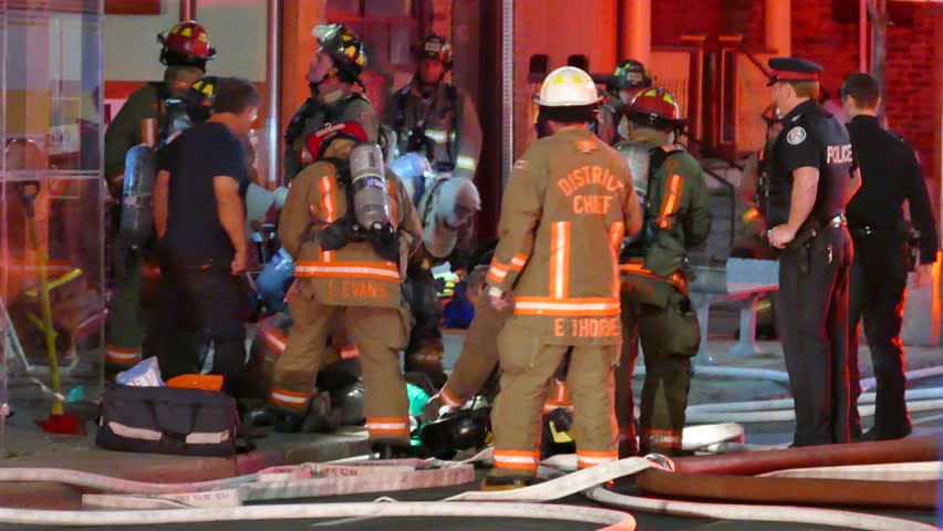 Toronto, Canada - June 2015 - 4K UHD - Group of firemen giving first aid and CPR to victim