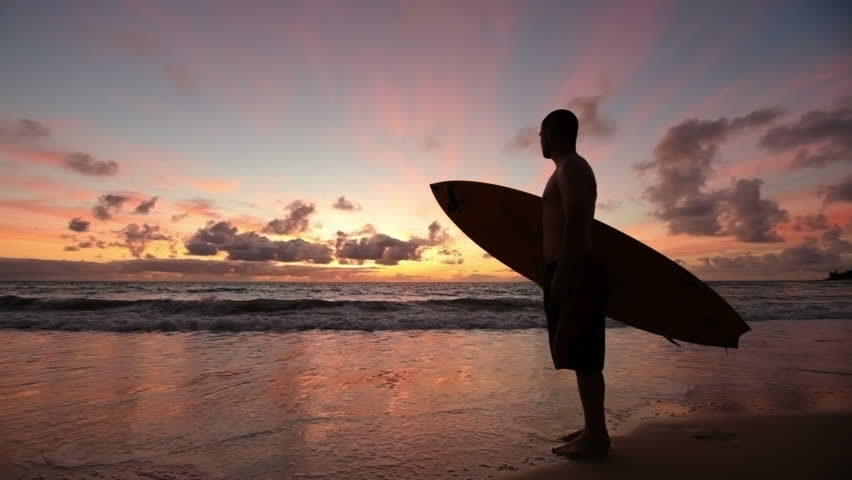 Cinemagraph - Surfer standing on beach at sunrise, Hawaii. Looping Motion Photo.