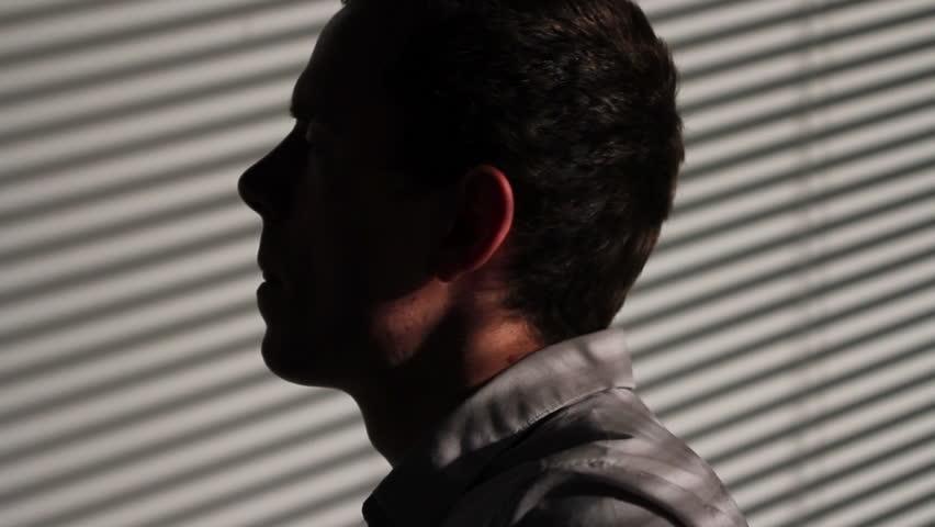 Worried man lit by window blinds, turn - HD stock footage clip