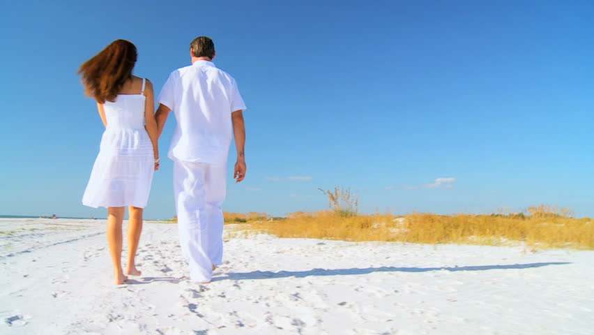 Attractive healthy couple enjoying time together walking barefoot on the beach filmed at 60FPS - HD stock footage clip