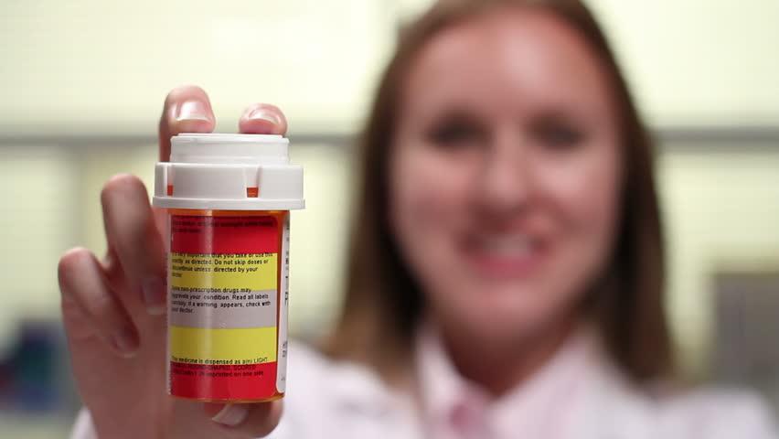 Pharmacist holding prescription bottle, shift focus - HD stock video clip