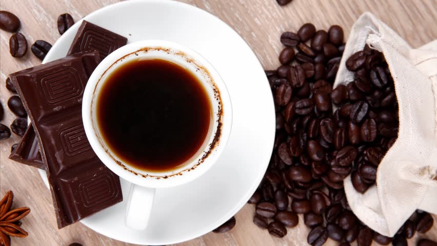sweet hot food: black coffee with dark chocolate and coffee beans in bag on wooden table 1920x1080 intro motion slow hidef hd