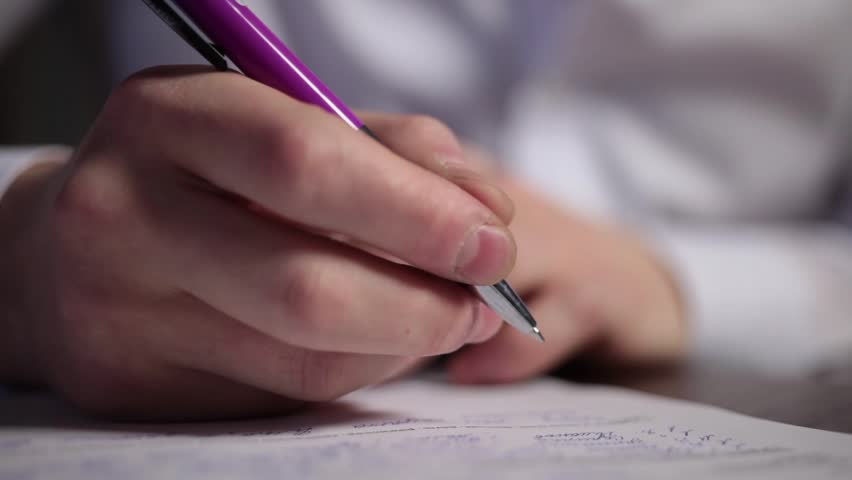 A man is writing description and signing a ducument