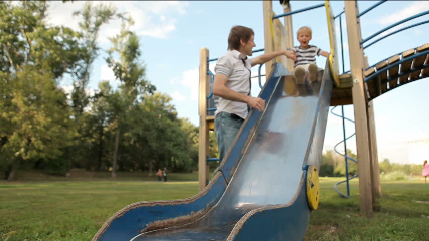 Young boy plays with father on the playground
