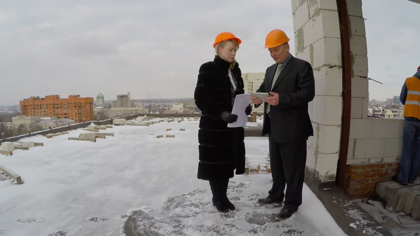 Male and female managers on construction of a skyscraper to read blueprints and a tablet. Construction in winter. In the background, unrecognizable builder working in an orange vest and helmet.