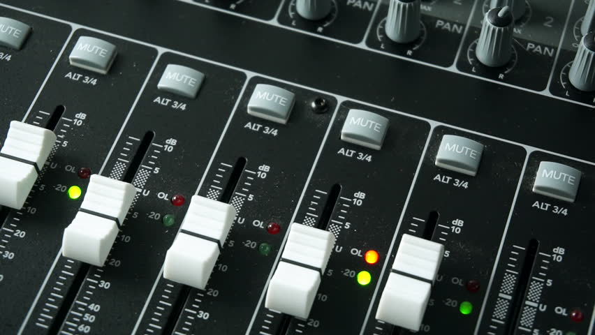 A sound engineer using a mixing desk or mixing console to mix a track in a recording studio. With level and overload lights, faders and pots / knobs.