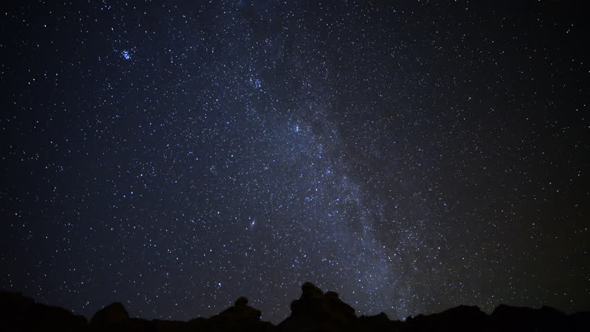 Astrophotography time lapse footage with pan left motion of meteorite burst & star trails over desert rock formation during Geminid Meteor Showers in 2015 at Red Rock Canyon State Park, California