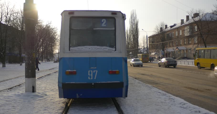 KONOTOP/UKRAINE - JAN 06 2016: Tram Station at Mir Avenue in Konotop City, Pople enter and Sits Inside Old Blue Tramcar, tram number 2, carema follows to a tram, half empty Tramcar, Cars are Driving