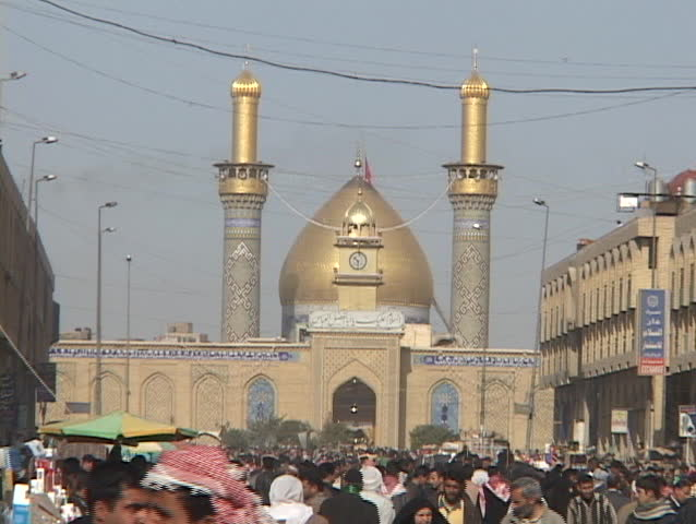 Crowds of Iraqis walk in front of a beautiful mosque in downtown Baghdad, Iraq.
