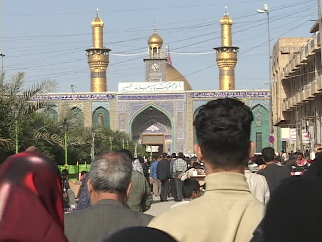 IRAQ - CIRCA 2003: Crowds of Iraqis walk toward a mosque circa in Baghdad, Iraq.